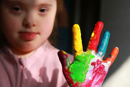 Down syndrome girl with painted hands